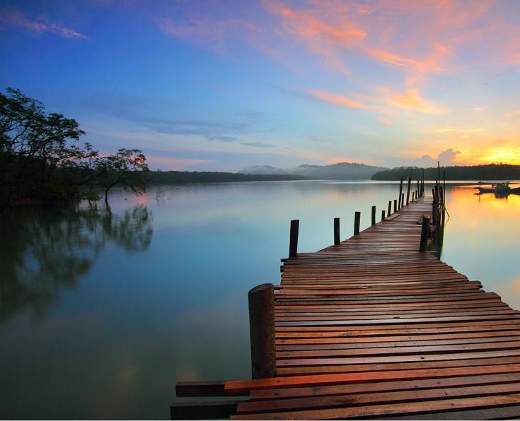 Passerelle en bois sur un lac au coucher du soleil