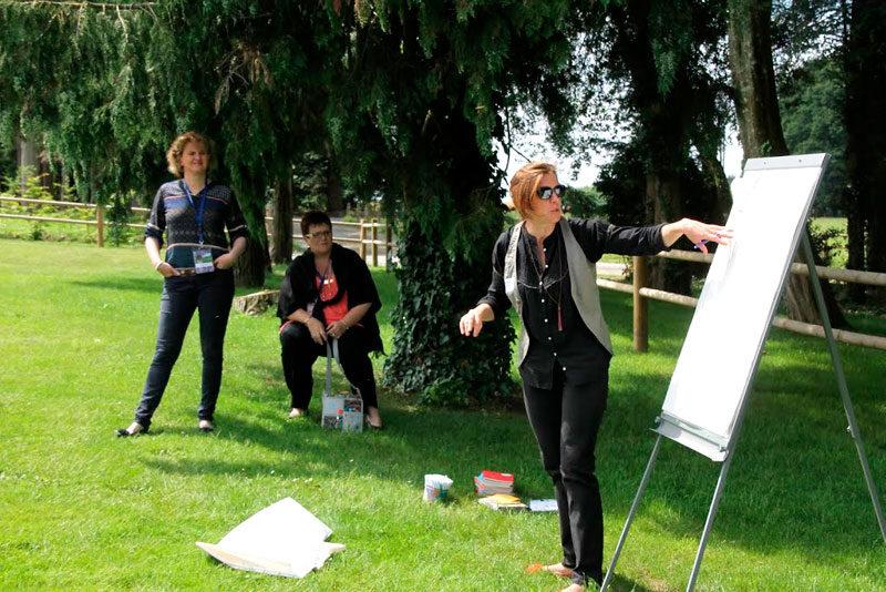 Corinne anime dans le jardin un atelier en créativité. Elle montre à 5 ou 6 personnes quelque chose écrit sur un paper-board